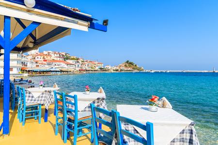 Tabelle con le sedie in taverna greca tradizionale nella città di Kokkari sulla costa dell'isola di Samos, Grecia Archivio Fotografico - 73946569