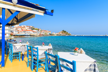 Tables with chairs in traditional Greek tavern in Kokkari town on coast of Samos island, Greece