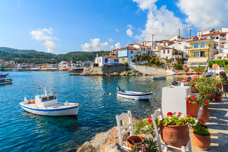 Flowers on shore with fishing boats in Kokkari port, Samos island, Greece 免版税图像