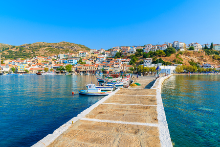 Pier in Pythagorion port with fishing boats in distance, Samos island, Greece 스톡 콘텐츠