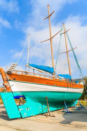 Traditional wooden sail boat in shipyard of small Greek marina, Samos island, Greece Stock Photo