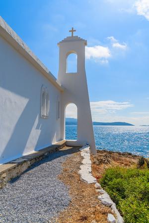 Tower of white Greek church in back light on coast of Samos island, Greece Stock Photo
