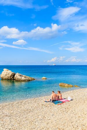 SAMOS ISLAND, GREECE - SEP 24, 2015: Couple of young people relaxing on beautiful Kokkari beach, Samos island, Greece