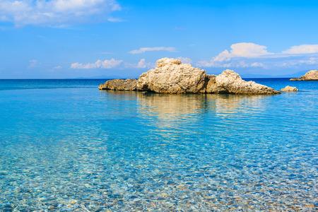 Rock in blue crystal clear sea water on beach of Samos island, Greece Stock Photo