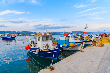 Colourful Greek fishing boats mooring in port at sunset time on Samos island, Greece