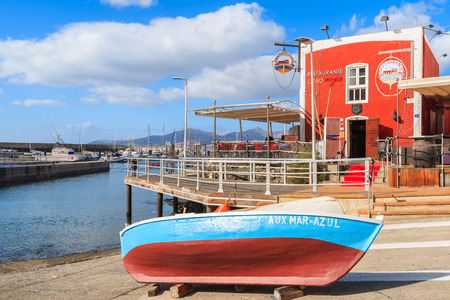 PUERTO DEL CARMENT PORT, LANZAROTE - JAN 17, 2015: colorful fishing boat in front of red restaurant building in Puerte del Carmen port. This town is popular holiday destination on Lanzarote island.