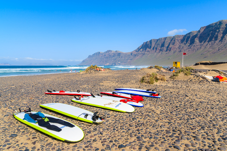 FAMARA BEACH, LANZAROTE - JAN 15, 2015: surfing boards on Famara beach which is famous for best ocean waves on Lanzarote island. Canary Islands are popular destination for water sport lovers.