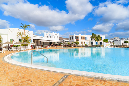 PLAYA BLANCA, LANZAROTE ISLAND - JAN 17, 2015: swimming pool of luxury apartment complex built in traditional Canary style on Lanzarote island. Editorial