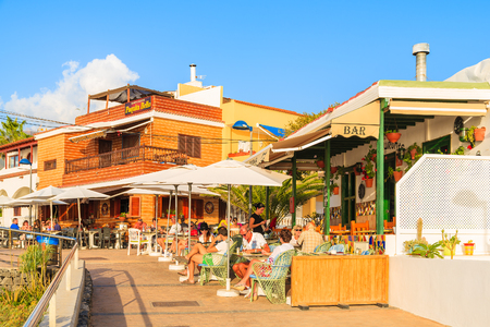 cana: LA CALETA, TENERIFE ISLAND - NOV 16, 2015: people sitting in restaurants in La Caleta fishing village on coast of Tenerife, Cana