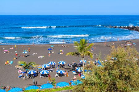 swimm: PUERTO DE LA CRUZ BEACH, TENERIFE ISLAND - NOV 16, 2015: A view of beach in Puerto de la Cruz with tourists sunbathing and swimm