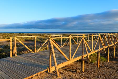 windsurf: Wooden footbridge walkway to beach near Morro Jable lighthouse in warm sunset light, Fuerteventura island, Spain Foto de archivo