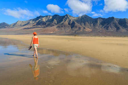 Young woman tourist in red shirt and hat walking on wet golden sand Cofete beach, Fuerteventura, Canary Islands, Spain Stock Photo