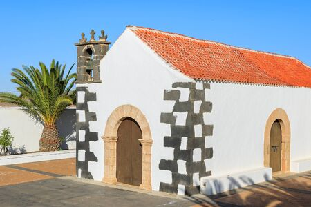 Palm trees and typical Canary style white church building in Tindaya village, Fuerteventura, Canary Islands, Spain
