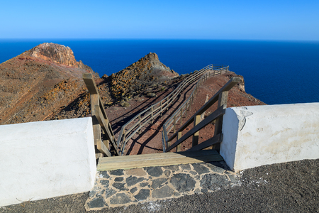 Steps to viewpoint on Punta Entellada near Las Playitas where tourists can see mountain cliff and ocean, Fuerteventura, Canary Islands, Spain