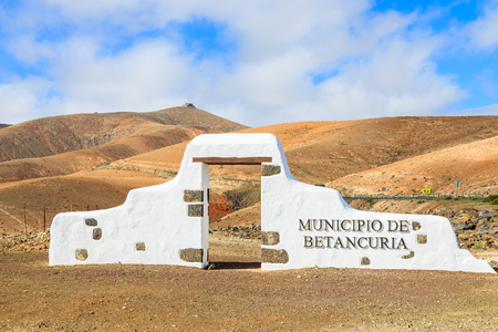 Typical municipality sign (white arch gate) near Betancuria village with desert mountain landscape in the background, Fuerteventura, Canary Islands, Spain Stock Photo