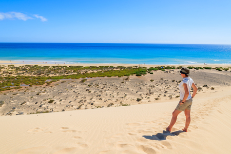 Young woman standing on sand dune on Sotavento beach on Jandia peninsula and looking at ocean, Fuerteventura, Canary Islands, Spain Stock Photo