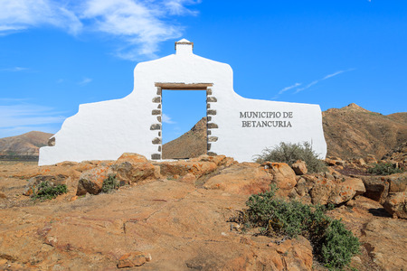 Traditional municipality sign (white arch gate) near Betancuria village with desert landscape in the background, Fuerteventura, Canary Islands, Spain Stock Photo