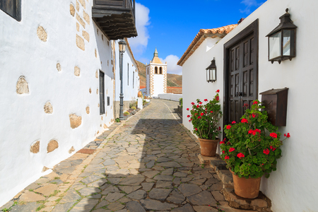Narrow street in Betancuria village with Santa Maria church tower in background, Fuerteventura, Canary Islands, Spain