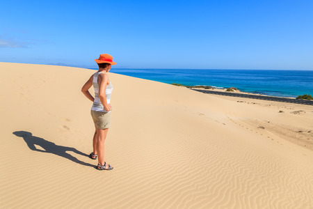 Young woman tourist standing on sand dune in Corralejo National Park and looking at ocean, Fuerteventura, Canary Islands, Spain
