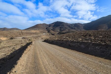 Unpaved road to Cofete beach from Morro Jable town and volcanic mountains in background, Fuerteventura, Canary Islands, Spain