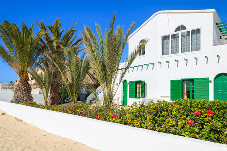 EL COTILLO, FUERTEVENTURA - FEB 5, 2014: White building of a holiday villa with green window shutters built in traditional Canary style in El Cotillo in northern part of Fuerteventura, Spain.