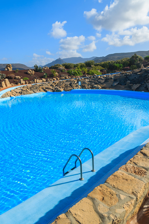 LA PARED, FUERTEVENTURA - FEB 7, 2014: swimming pool in a luxury hotel with mountains in the background. Many tourists spend vacation on Canary Islands in winter time. Stock Photo