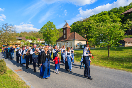 GLASING VILLAGE, AUSTRIA - APR 30, 2016: music band people walking in a parade on street during May Tree celebration. In Germany and Austria the maypole is a tradition going back to the 16th century. Editorial