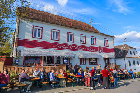 GLASING VILLAGE, AUSTRIA - APR 30, 2016: people sitting at tables of local restaurant during May Tree celebration. In Germany and Austria the maypole is a tradition going back to the 16th century.