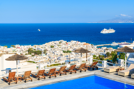MYKONOS ISLAND, GREECE - MAY 17, 2016: Sunbeds alongside of a hotel pool and view of Mykonos town, Cyclades islands, Greece.