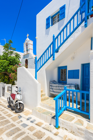 MYKONOS TOWN, GREECE - MAY 15, 2016: Scooter parked in front of a typical white Greek house in Mykonos town, Mykonos island, Greece.