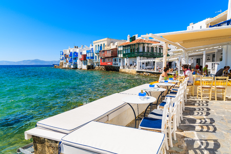 LITTLE VENICE, MYKONOS ISLAND - MAY 16, 2016: people dining in typical Greek tavern in Little Venice part of Mykonos town, Mykonos island, Greece.