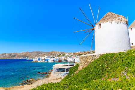 White traditional windmill overlooking Mykonos port, Cyclades islands, Greece