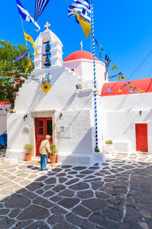 MYKONOS TOWN, GREECE - MAY 16, 2016: old Greek man standing in front of a church and looking at obituaries, Mykonos town, Cyclades islands, Greece.