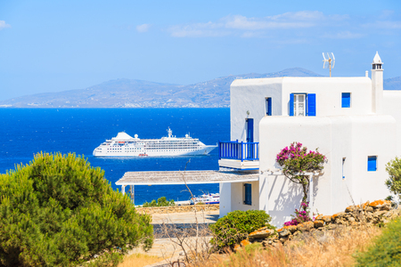 White typical Greek house and cruise ship on sea in background, Mykonos island, Greece