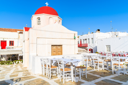 Typical Greek white church and tavern tables in Mykonos town, island, Greece