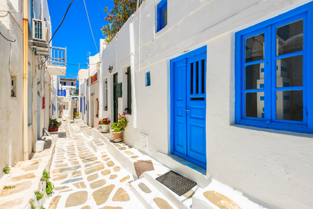 Typical white Greek houses with blue doors and windows on street of beautiful Mykonos town, Cyclades islands, Greece