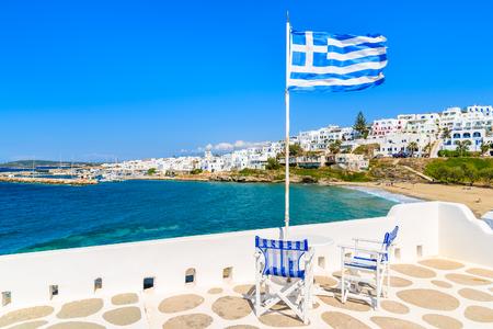 Stühle mit Tabelle auf einer Terrasse mit griechischer Flagge in Naoussa-Dorf, Paros-Insel, Griechenland