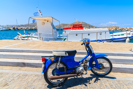 classic blue scooter parking in Naoussa port on Paros island, Greece.