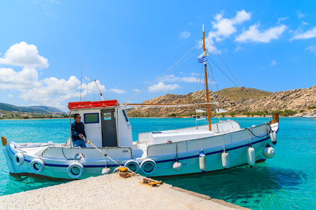 PAROS ISLAND, GREECE - MAY 20, 2016: fisherman in typical fishing boat mooring in secluded sea bay on Paros island, Greece.