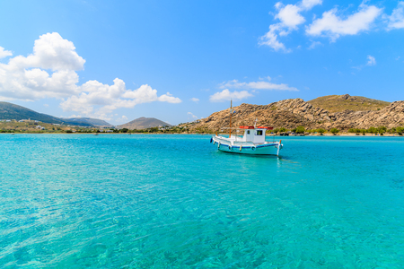 Typical Greek fishing boat sailing on turquoise sea water on Paros island, Greece