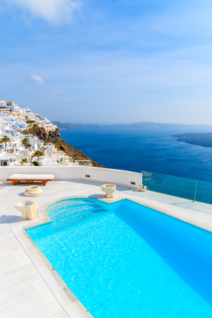 View of caldera and luxury swimming pool in foreground, typical white architecture of Imerovigli village on Santorini island, Greece.
