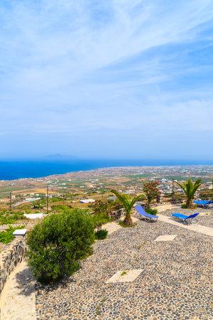 Sunbeds on sunny terrace with view of coast, Santorini island, Greece Editorial