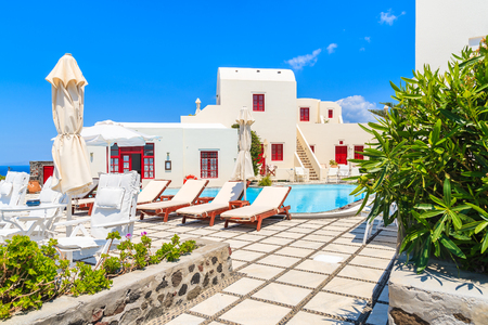OIA VILLAGE, SANTORINI ISLAND - MAY 23, 2016: Typical greek style apartment hotel with pool in Oia village, Santorini island, Greece.
