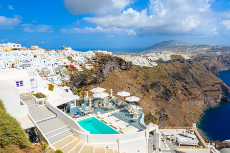 View of luxury boutique hotel with swimming pool in Imerovigli village on Santorini island, Greece