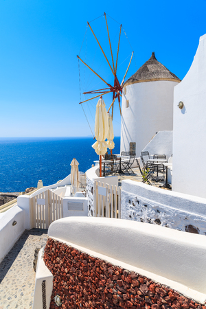 Typical white windmill on street of Oia village with blue sea in background, Santorini island, Greece