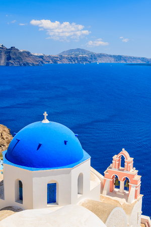 Famous blue dome of a church in Oia village and view of blue sea with caldera on Santorini island, Greece