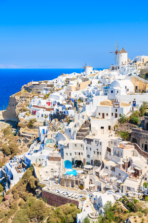 View of famous windmill and white houses in Oia village on Santorini island, Greece