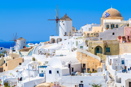 White houses and traditional windmill in Oia village on Santorini island, Greece Stock Photo