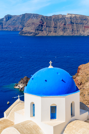 View of famous church with blue dome against blue sea with caldera in Oia village, Santorini island, Greece