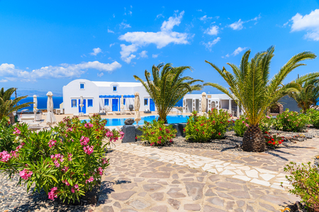 OIA VILLAGE, SANTORINI ISLAND - MAY 23, 2016: Typical Greek style holiday apartments in a beautiful garden with palm trees in Oia village on Santorini island, Greece.